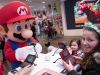 In this photo provided by Nintendo of America, Gia P. from Bronx, NY and Alyssa P. from Bronx, NY meet with Mario at the Nintendo NY store in Rockefeller Plaza on Friday, March 24. Fans gathered to celebrate the launch of Mario Sports Superstars, an action-packed Nintendo 3DS game that finds players competing in five full-featured sports: Baseball, Soccer, Golf, Tennis and Horse Racing.